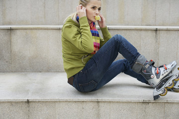 Young woman wearing inline skates listening to music about earphones sitting on staircase
