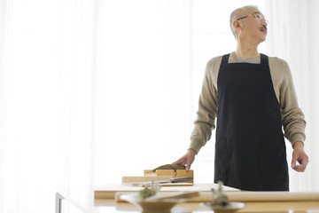Mature man in kitchen, looking away, copy space