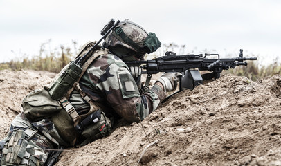Machine gunner of 1st Marine Infantry Parachute Regiment RPIMA firing from defensive position trench, profile side view