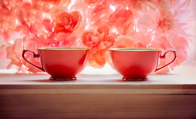 two red teacups pink floral background