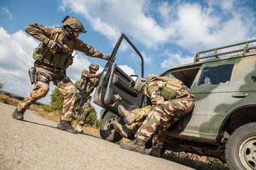Squad of elite french paratroopers of 1st Marine Infantry Parachute Regiment RPIMA detaining terrorist in the car, low angle view