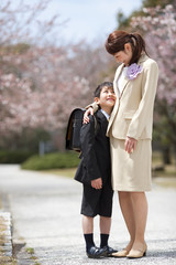 Elementary school boy with Mother under cherry blossoms