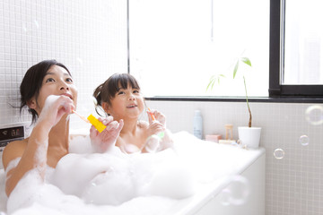 Mother and daughter taking bubble bath