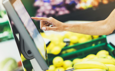 buyer weighs the yellow bananas and points the fingers on the screen electronic scales, woman shopping healthy food in supermarket blur background, female hands buy nature products in store grocery
