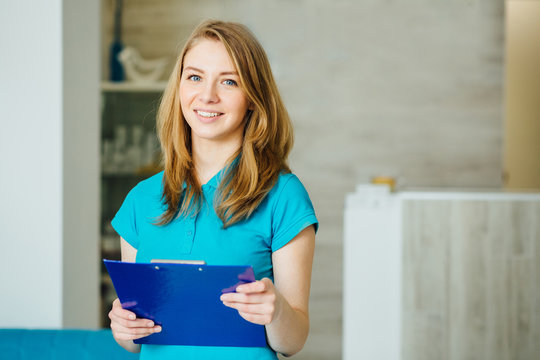 Portrait of young beautician. Young female receptionist holding blue folder and standing in nice modern hall of cosmetologycal clinic. Beauty salon interior