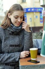 Beautiful girl thinks of drinking coffee or making a phone call