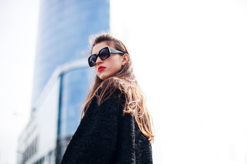 Fashion portrait of young elegant confident woman outdoor. black jacket, red lips and sunglasses.
