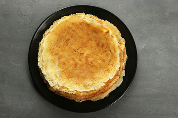 Plate with tasty pancakes on grey table