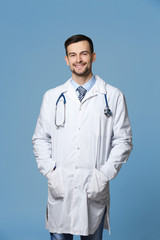 Handsome young doctor with stethoscope on grey background