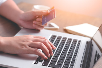 Close up hand holding credit card and using laptop. Online shopping