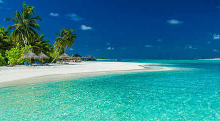 Palm trees and beach umbrelllas over lagoon and white sandy beach, Maldives