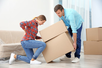 Woman suffering from ache while moving boxes in room
