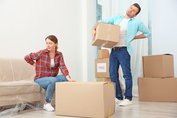 Couple suffering from ache while moving boxes in room