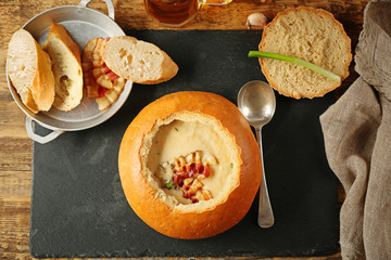 Delicious cream soup in bread on table