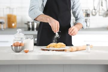 Man preparing pasta on kitchen table