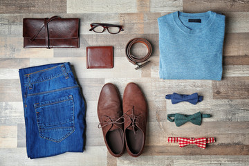 Set of stylish male clothes on wooden background