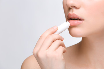 Woman applying hygienic lip balm on light background Wall mural