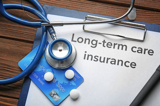 Text LONG-TERM CARE INSURANCE on clipboard with pills, stethoscope and credit card on wooden table closeup