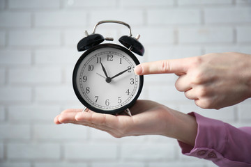 Female hands holding alarm clock on white brick wall background