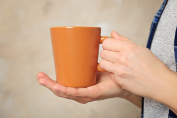 Blank color cup in hands, closeup