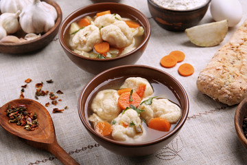 Portions of delicious chicken and dumplings on dining table
