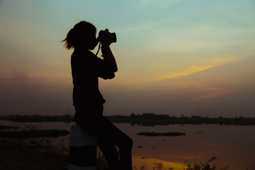 Silhouette women Nature photographer with digital camera on the mountain and lake
