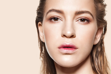 Close-up face of fashionable girl with natural make-up and clean beautiful skin looking at camera on beige background