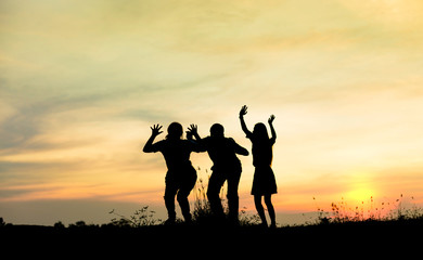Silhouette group of friends having fun jumps on sunset and mountains backdrop