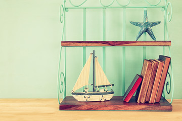 Vintage shelf with boat, old books and starfish