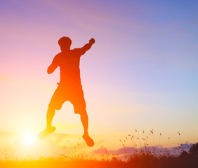 Silhouette of jumping man on sunrise background. The concept happy.