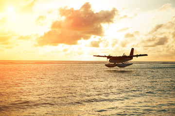 Summer sunrise with seaplane. Landing seaplane on the seashore. Calm scenery on morning sea.