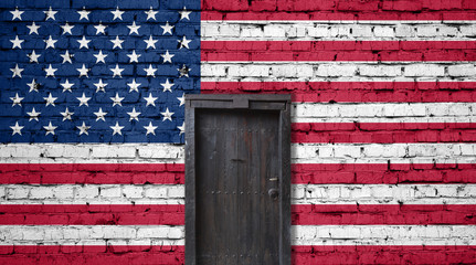 American flag on brick wall. Closed door in a wall