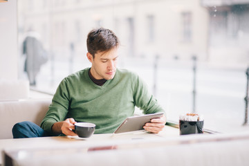 Young man using tablet computer and drinking coffee in cafe