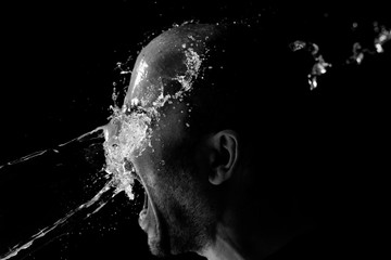 Portrait of a man being thrown water in the face against a black background