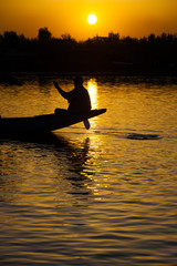 Shikara Boatman Silhouette on Dal Lake at Evening Sunset in Srinagar, Kashmir, India