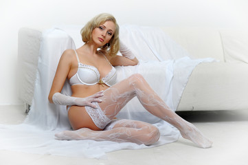 Cute sexy blonde woman like an angel. Sensual girl in white lingerie smiling. White background.