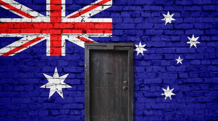 Australia flag on brick wall. Closed door in a wall