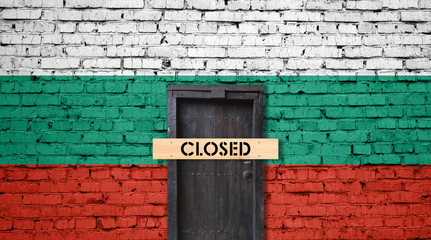 Bulgaria flag on brick wall with closed door and Closed sign