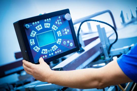 Worker programming print screening machine on the monitor.