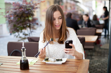 Young woman texting eating sushi outdoor restaurant