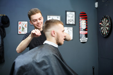 Great time at barbershop. Cheerful young bearded man getting haircut by hairdresser while sitting in chair at barbershop
