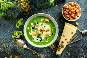 Dietary Broccoli smooth cream soup with sprinkle of sunflower seeds, parsley leaves and croutons on stone table.