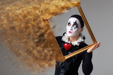 Woman in disguise harlequin in the picture frame. Photo manipulation