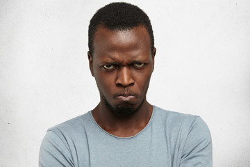 Studio portrait of displeased, angry, grumpy and pissed off young African American male looking and frowning at camera, pursing lips, having bad mood, feeling dissatisfied and furious with something