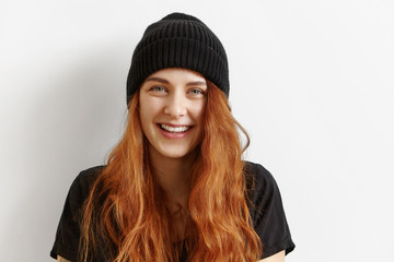 Close up shot of beautiful and charming young redhead European woman with messy loose hairstyle wearing black hat and t-shirt indoors, looking at camera with cute charismatic smile. Horizontal