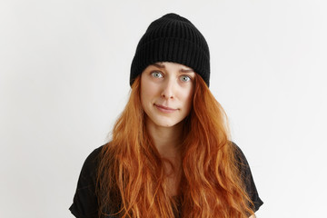 Indoor studio shot of cute redhead hipster girl wearing t-shirt and hat having indignant and blaming look, frowning and grimacing, pursuing her lips, doesn't approve something. Body language