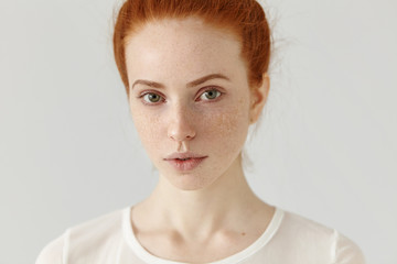 Close up studio shot of beautiful charming redhead European model with healthy freckled skin looking at camera with faint smile, posing indoors against blank wall background, wearing white t-shirt