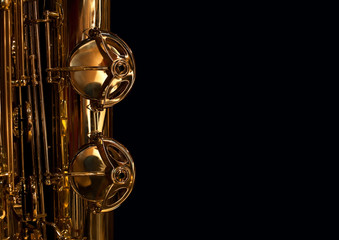 Wall Mural - Fragment of saxophone valves in gold tones on a black background
