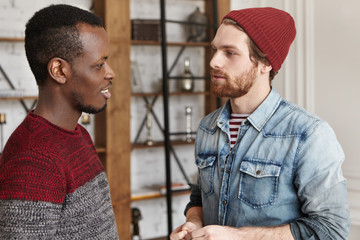 People and interracial friendship concept. Candid shot of two stylish male best friends of different races standing opposite each other and talking against modern restautant interior background