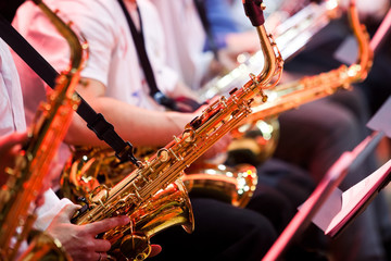 Saxophone in the hands of a musician in an orchestra closeup